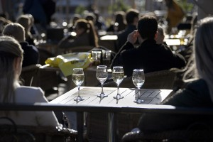People enjoy the sun in an outdoor restaurant in Stockholm